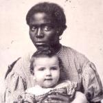 Black female slave woman holding white baby.