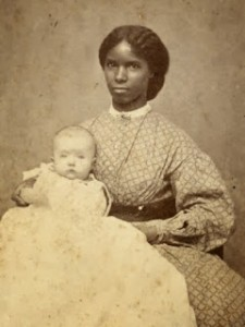 Black female slave woman holding white baby.